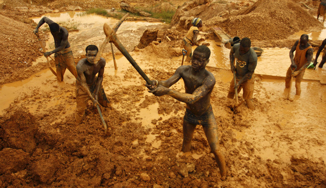 Miners dig for gold in an open-pit concession near Dunkwa
