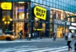 Pedestrians pass in front of a Best Buy Co. store in this photo taken with a tilt-shift lens in New York, U.S., on Sunday, June 12, 2011. Best Buy Co., the world's largest consumer electronics retailer, is scheduled to announce quarterly earnings on June 14 before the opening of U.S. financial markets. Photographer: Chris Goodney/Bloomberg via Getty Images
