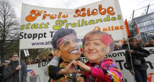 Protesters wearing masks depicting German Chancellor Angela Merkel and U.S. President Barack Obama as they demonstrate against Transatlantic Trade and Investment Partnership (TTIP) agreement ahead of Obama's visit in Hanover, Germany April 23, 2016.  REUTERS/Kai Pfaffenbach
