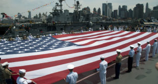 u-s-navy-marine-corps-and-coast-guard-personnel-unfurl-an-american-flag-on-the-flight-deck-of-the-intrepid-sea-air-space-museum-at-a-memorial-day-ceremony-during-fleet-week-new-york