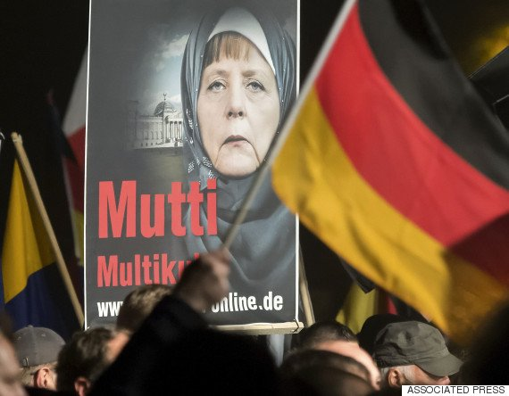 A banner reading 'Mum multiculti' and depicting a manipulated image German Chancellor Angela Merkel is carried by a protester behind the German flag as some thousands of people take part in a demonstration initiated by the Alternative for Germany (AfD) party against what they call the uncontrolled immigration and asylum abuse in Erfurt, central Germany, Wednesday, Oct. 28, 2015. (AP Photo/Jens Meyer)
