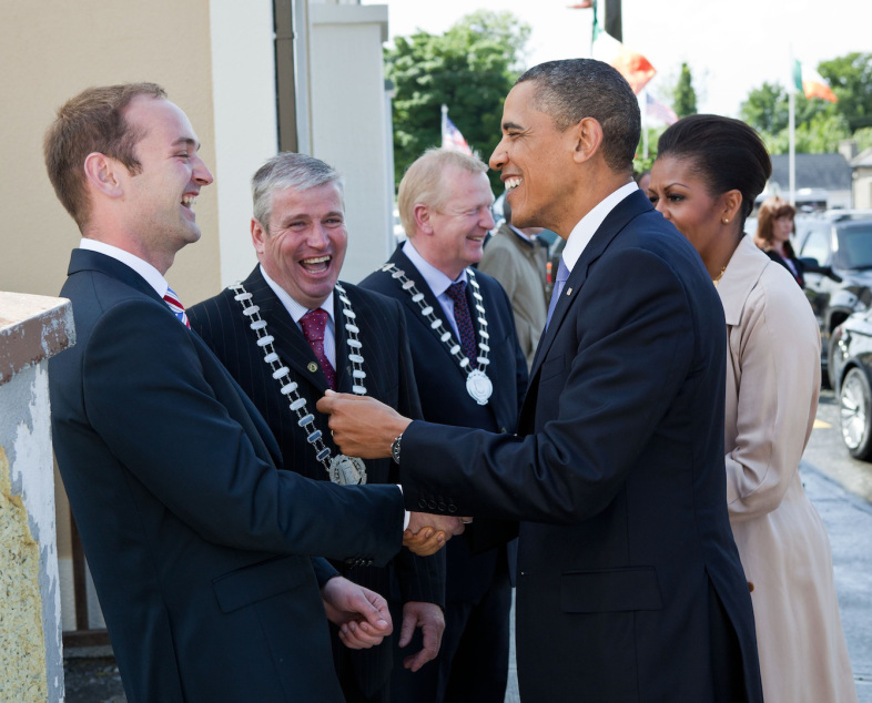 President Barack Obama and First Lady Michelle Obama greet Henry Healy, the President's distant cousin, after arriving in Moneygall, Ireland, May 23, 2011. The President and First Lady were also welcomed by Counselor Danny Owens, Chair Offaly County, and Counselor John Kennedy, Chair Tipperary County, center. (Official White House Photo by Pete Souza) This official White House photograph is being made available only for publication by news organizations and/or for personal use printing by the subject(s) of the photograph. The photograph may not be manipulated in any way and may not be used in commercial or political materials, advertisements, emails, products, promotions that in any way suggests approval or endorsement of the President, the First Family, or the White House.