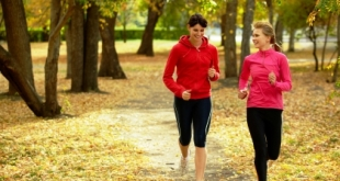 Two girls racing in autumn park