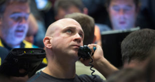 A trader fills orders Monday in the Standard
